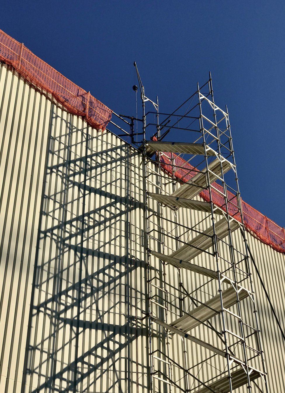 Scaffolding rises up along the side of a building and is framed against a blue sky