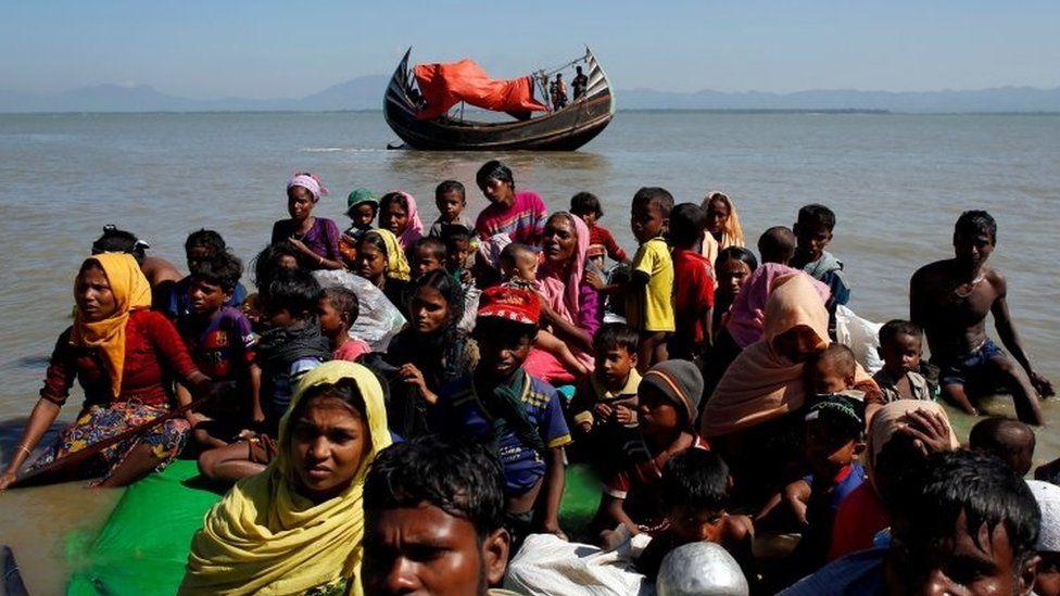 "Rohingya refugees sit on a makeshift boat as they get interrogated by the Border Guard Bangladesh after crossing the Bangladesh-Myanmar border, at Shah Porir Dwip near Cox""s Bazar, Bangladesh"