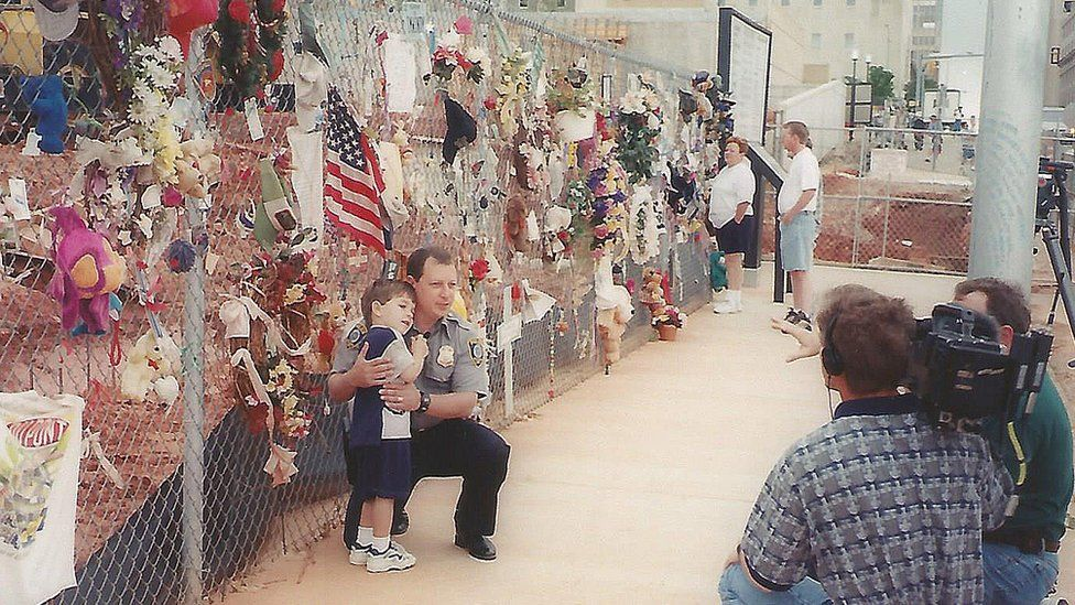 Kevin pictured with son at memorial fence years after blast