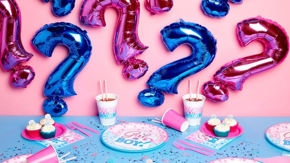 Gender reveal party merchandise, including inflatable blue and pink question marks, party plates and confetti