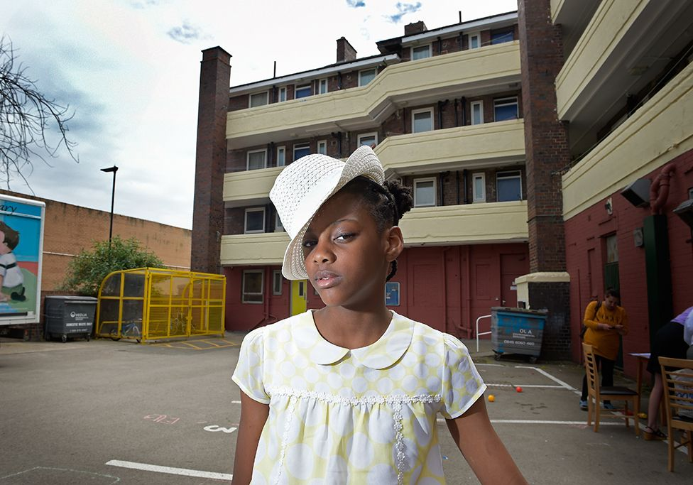 A girl poses for a portrait in a residential car park whilst wearing a hat