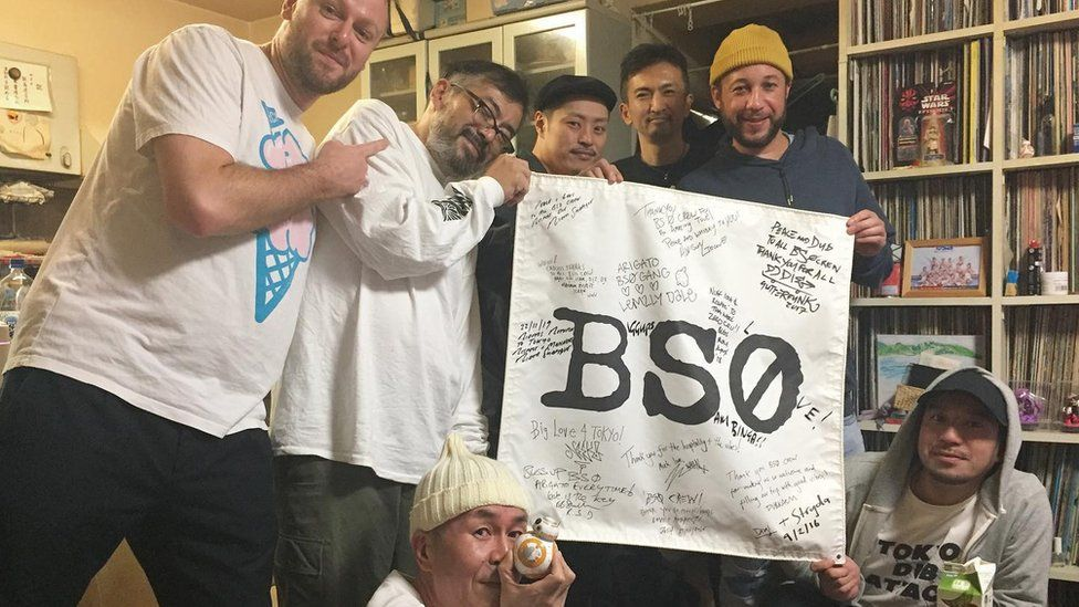 Image of Bristol artists and Mr Iijima holding flag reading BS0.