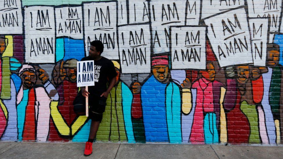 Xavier Hibler leans against a mural while marching through downtown during a Fight for $15 rally on April 4, 2017 in Memphis, Tennessee. About 1,000 people marched through downtown Memphis from City Hall to the National Civil Rights museum on the 49th anniversary of Dr. Martin Luther King, Jr.'s assassination