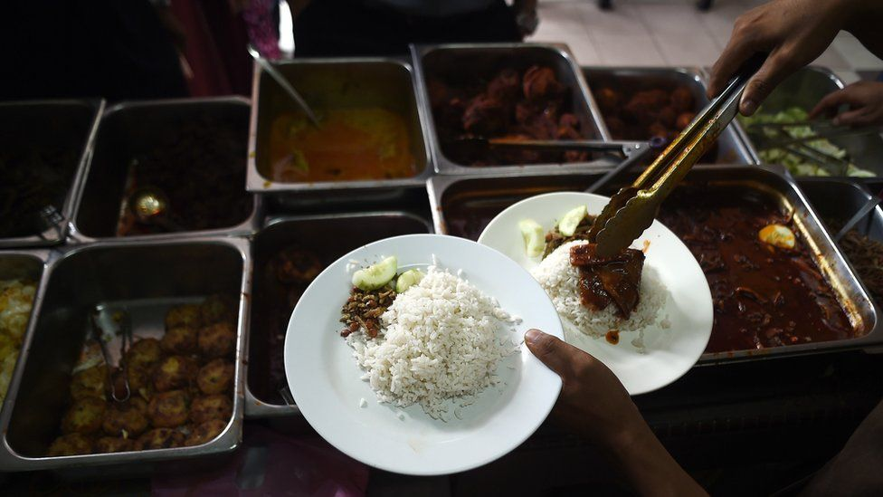A stall assistant serves up nasi lemak in Kuala Lumpur