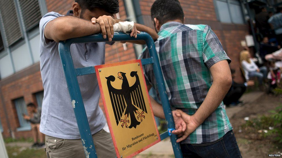 Asylum seekers wait in front of the Federal Office for Migration and Refugees (BAMF) in Berlin's Spandau district, Germany (17 August 2015)