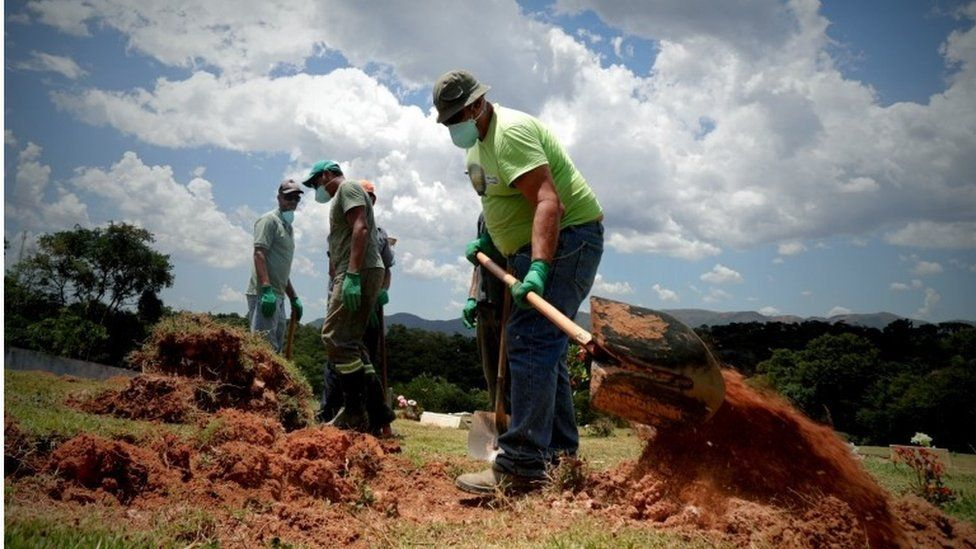 Men dig pits to bury victims of the dam accident