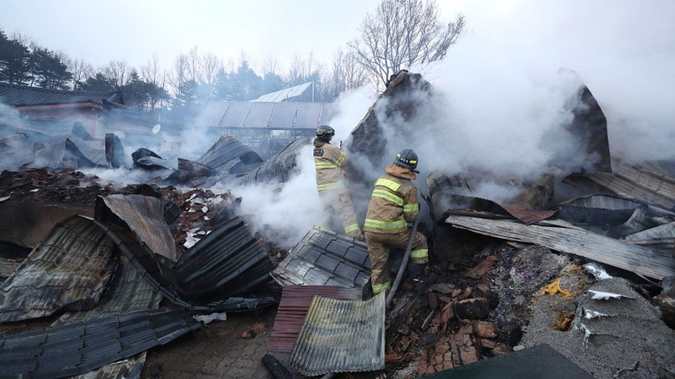 Firefighters try to extinguish a still burning house gutted by a massive forest fire in Sokcho, South Korea, on 5 April 2019