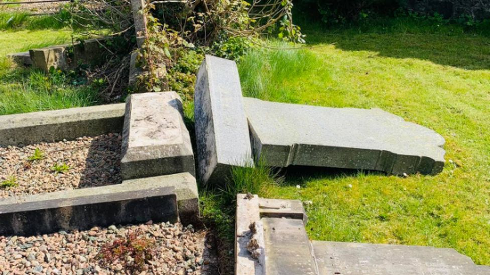 One of the damaged gravestones shown from the side, knocked off its base and lying on the ground