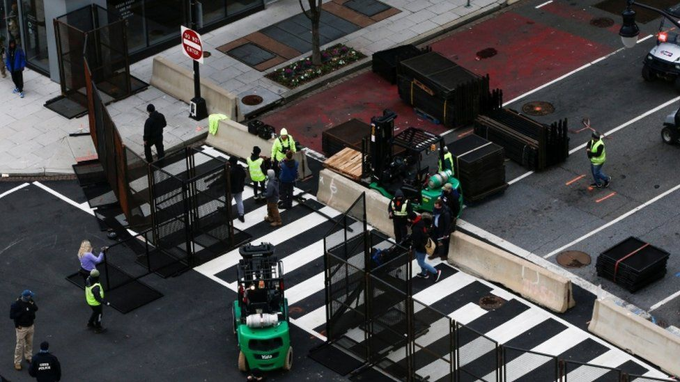 Workers place barricades to control access ahead of US President-elect Joe Biden's inauguration, in Washington, DC