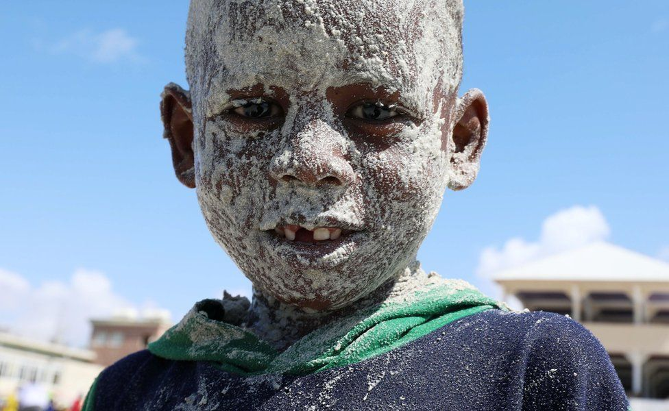 A Somali boy covers his face with sand at the Liido Beach during the last Friday ahead of the Muslim holy month of Ramadan, amid the coronavirus disease (COVID-19) pandemic in Mogadishu, Somalia April 9, 2021.