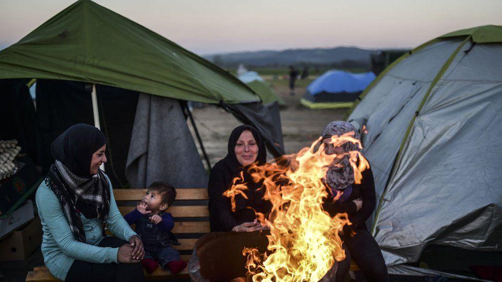 Syrian refugee women gather around bonfire at makeshift camp on Greek-Macedonian border. March 31, 2016