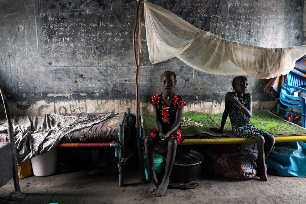 Displaced girls sit on a bed in a classroom, in a school now occupied by IDPs (Internally Displaced People) after heavy rains and floods