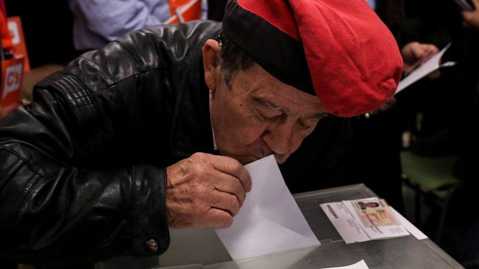 Man in traditional Catalan cap votes