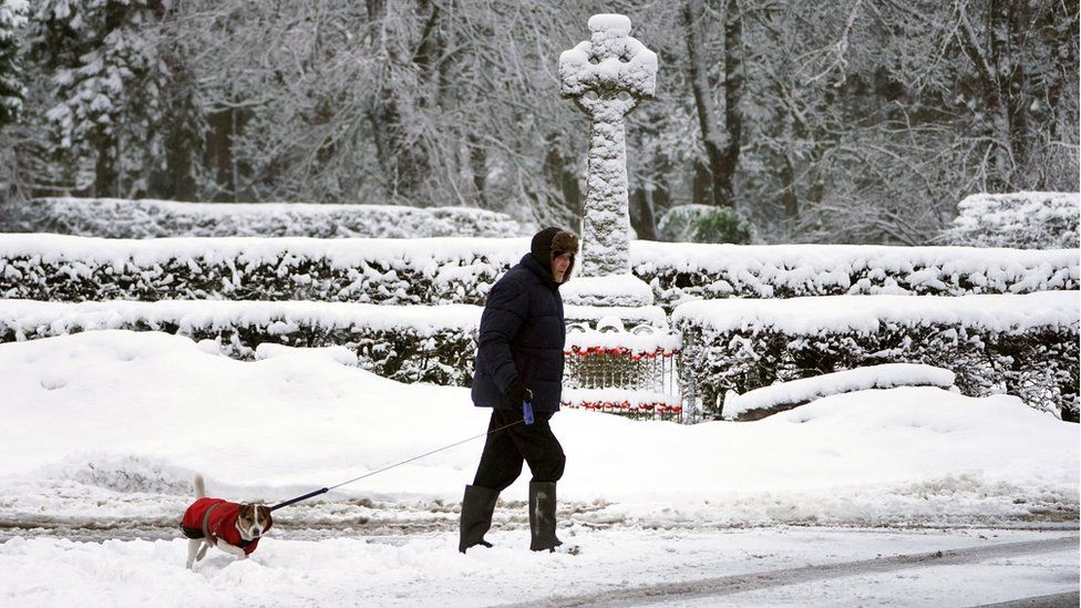 A man walks his dog through snow-covered roads in Allenheads, Northumberland.