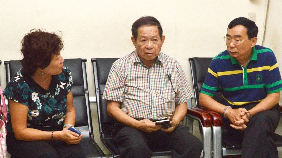 Two Chinese nationals, a consular officer (L) and her husband (R, with handcuffs), suspects in the shooting of Chinese consul general Song Ronghua at a restaurant, talk to an interpreter (C) at a police station in Cebu City, central Philippines.