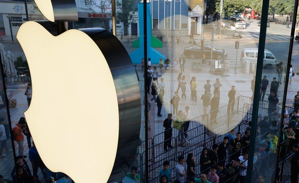 A window reflection of customers queue up outside an Apple store in Beijing