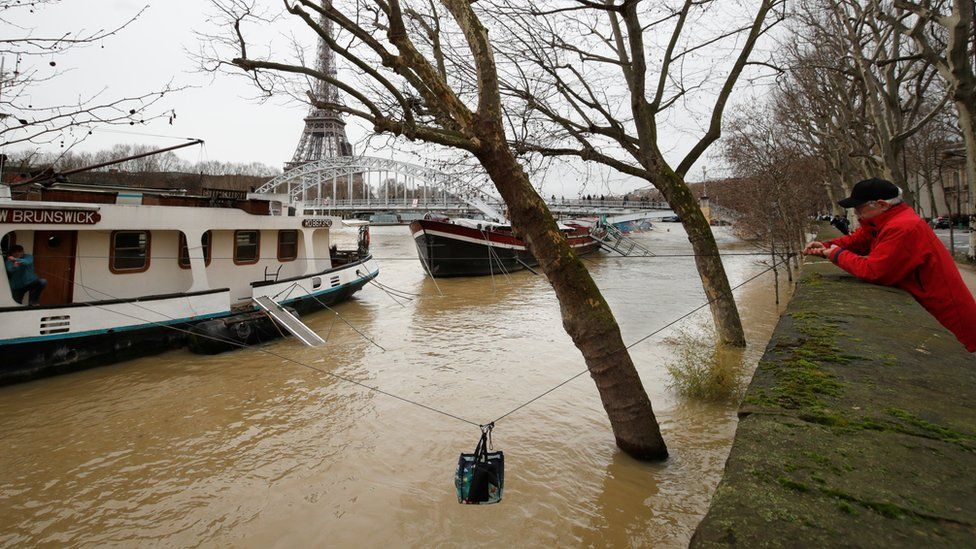A man uses a rope to transfer a bag of supplies to his friend who lives on a houseboat as the banks of the Seine River are flooded after days of rain throughout the country and in Paris, France 25 January 2018 .