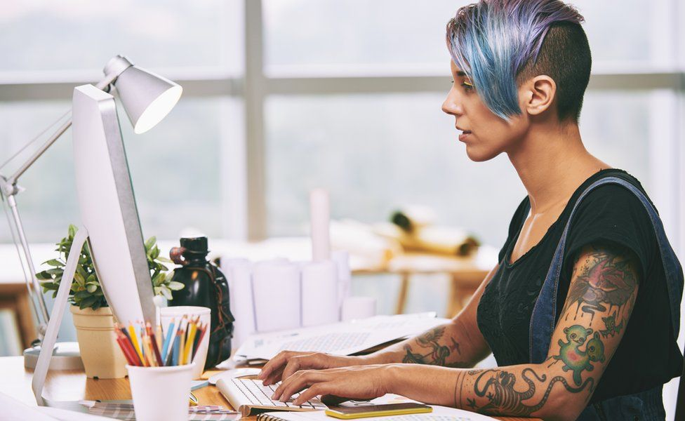 Tattooed woman at a computer