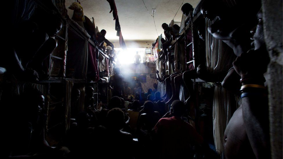 Prisoners cram shoulder to shoulder to watch TV in their crowded cell inside the National Penitentiary in downtown Port-au-Prince