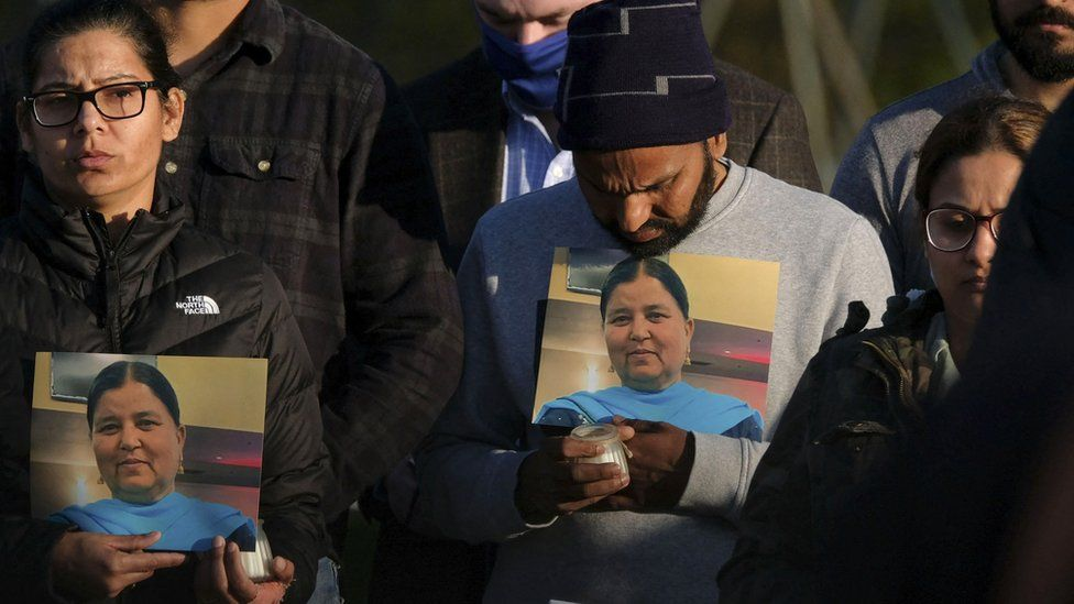 Family members show pictures of Jaswinder Kaur at a vigil
