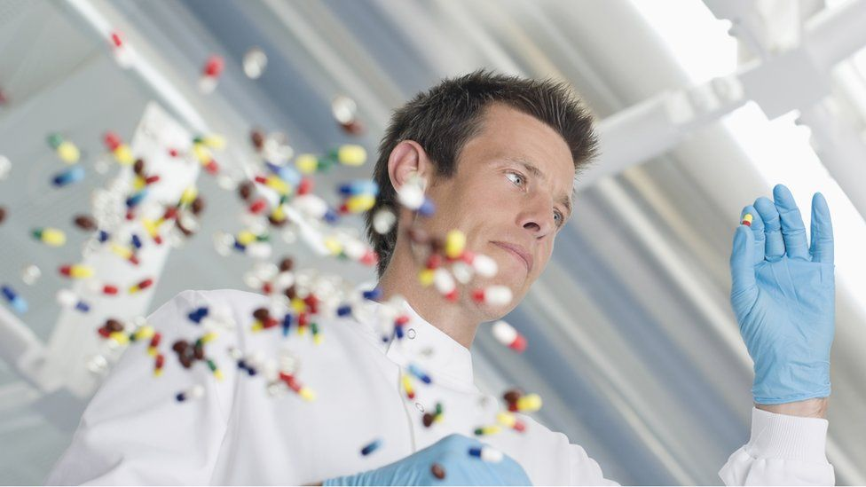 Pills being examined by a man