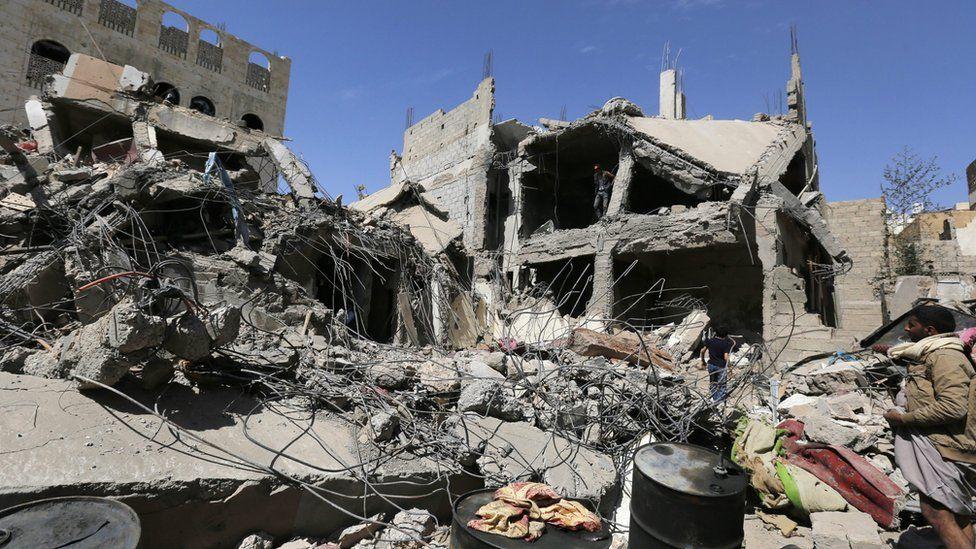 Yemenis inspect the scene of Saudi-led coalition air strikes in Sanaa (22 September 2015)