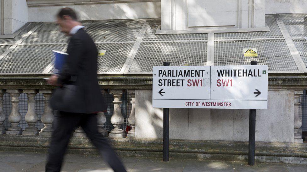 Man walking past Whitehall signs