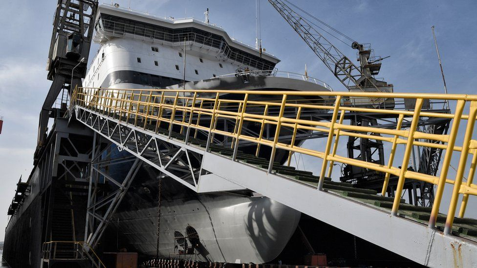 A large ship in dry dock is worked on in this photo from late 2018