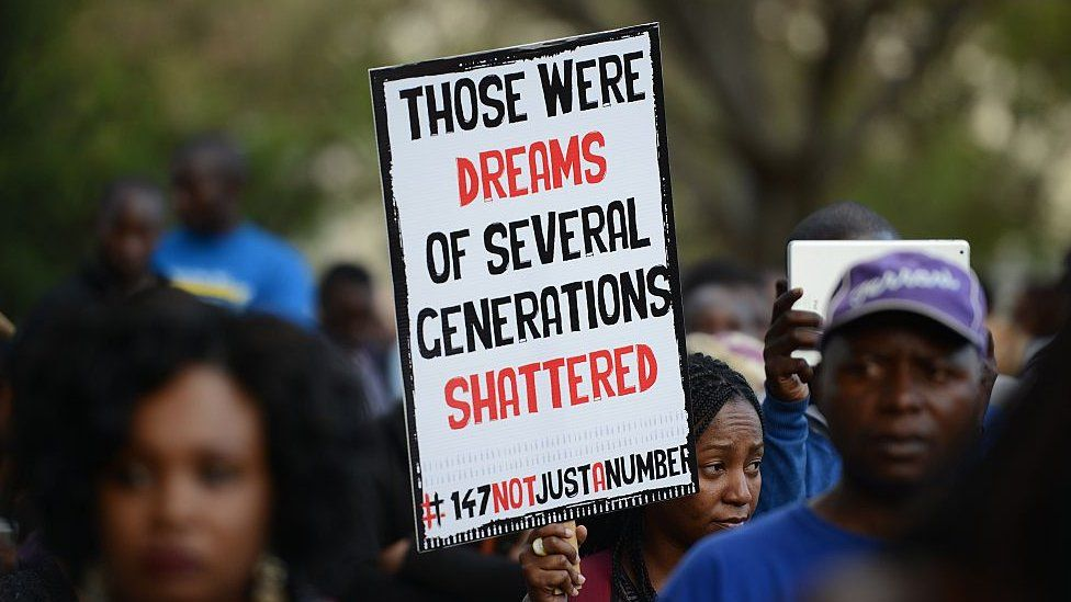 """A woman walks with a placard that reads """"Those were dreams of several generations shattered"""""""