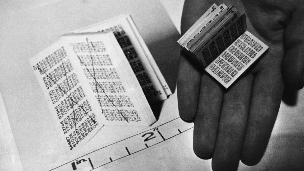A codebook full of tiny numbers, held in an open palm