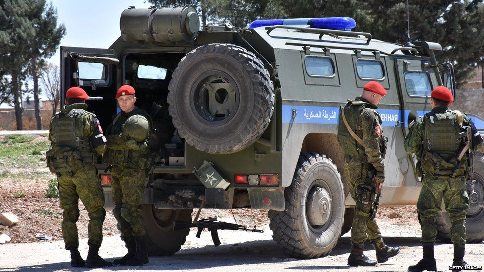 Members of the Russian military police stand guard in the northern city of Manbij