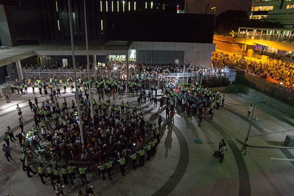 Student pro-democracy demonstrators are surrounded by police after storming into a courtyard outside Hong Kong's legislative headquarters on 26 September 2014.