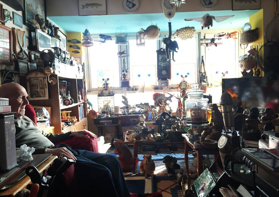 Derek Bather sits in a room surrounded by memorabilia of his life