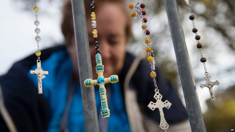 Lupe Cantu, of McAllen Valley, Texas, hangs rosary beads on a barricade along Benjamin Franklin Parkway as she waits for Mass delivered by Pope Francis, Sunday, Sept. 27, 2015, in Philadelphia