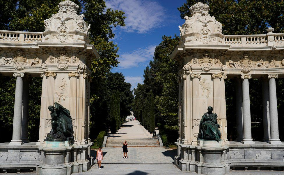 A woman takes pictures at Retiro Park on the day that Unesco added Madrid's historic Paseo del Prado boulevard and Retiro Park to its list of world heritage sites, in Madrid, Spain, 25 July 2021