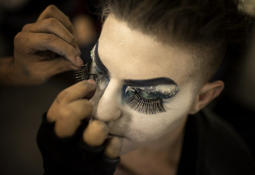 A make-up artist applies fake eyelashes to Elias