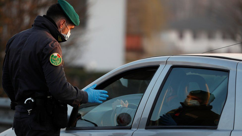 A member of the Guardia di Finanza wearing a face mask stops a car, amid a coronavirus outbreak in northern Italy