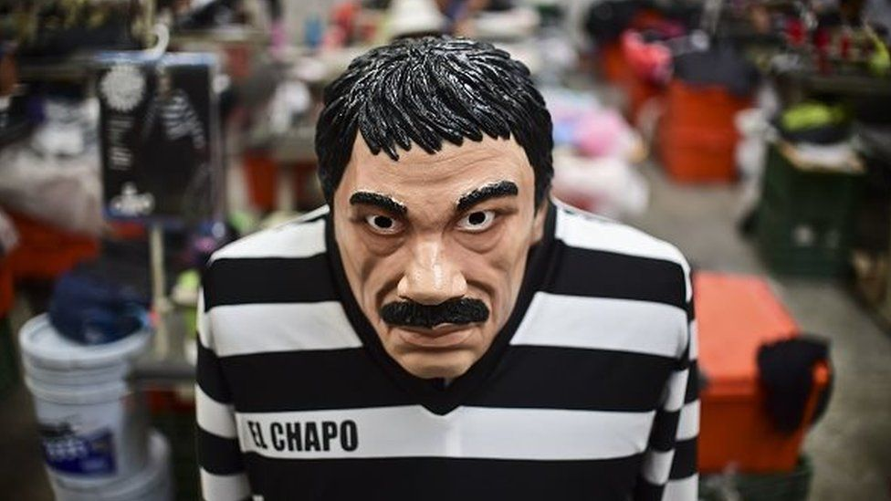 A costume and a mask representing Mexican drug trafficker Joaquin Guzman are pictured in a factory of costumes and masks, on October 16, 2015, in Jiutepec, Morelos State.