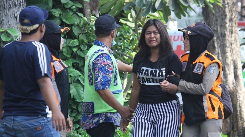 Police assist a woman looking for family members near the site of a blast at the Pentecost Church Central Surabaya in Surabaya, East Java, Indonesia, 13 May