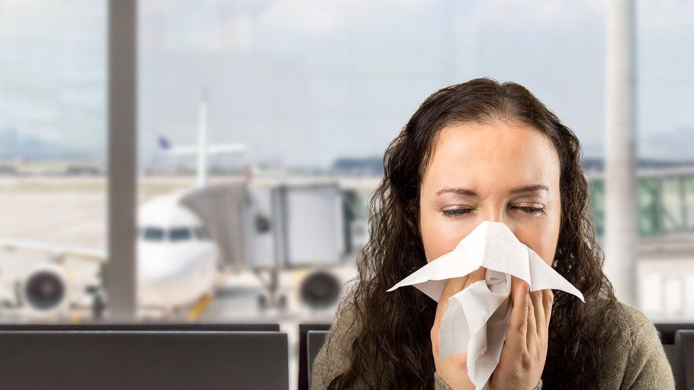 Woman coughing at an airport