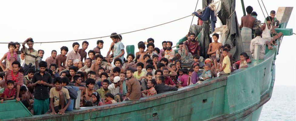 Hundreds of migrants, including Myanmar Rohingya Muslims, sit on their boat as they wait to be rescued by Aceh fishermen off East Aceh, Indonesia. 20 May 2015.