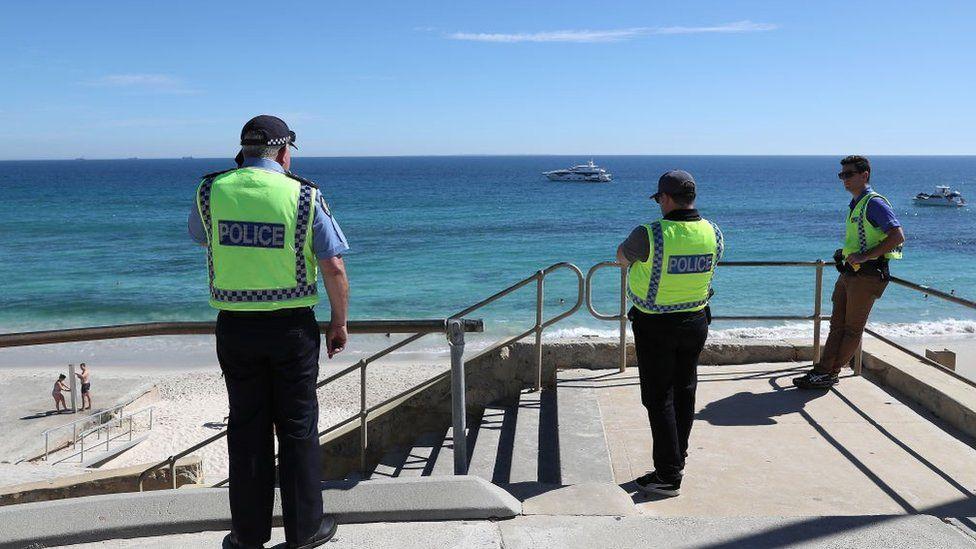 Police officers patrol Cottesloe Beach in Perth, Australia