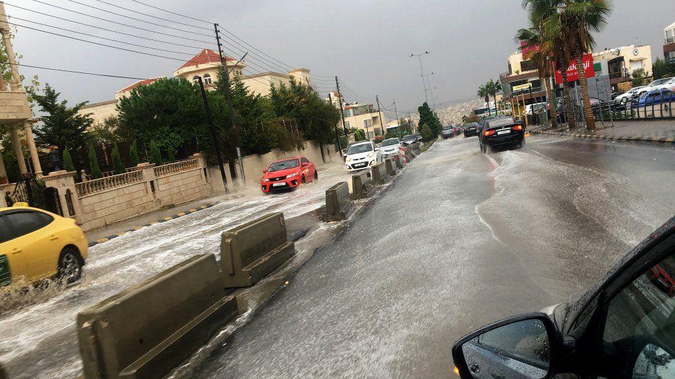 Vehicles drive through rain water after a sudden thunderstorm, at a street of Amman, Jordan, 25 October 2018