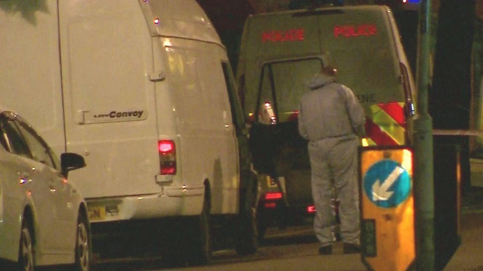 Forensic officer looking at van