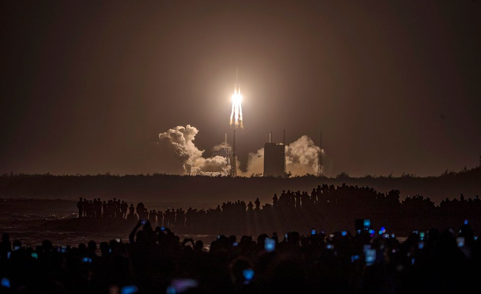 People watch a Long March 5 rocket carrying the Chang'e-5 lunar probe, in Wenchang, China