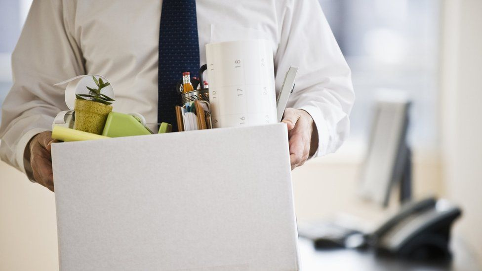 A man holds a box of work things
