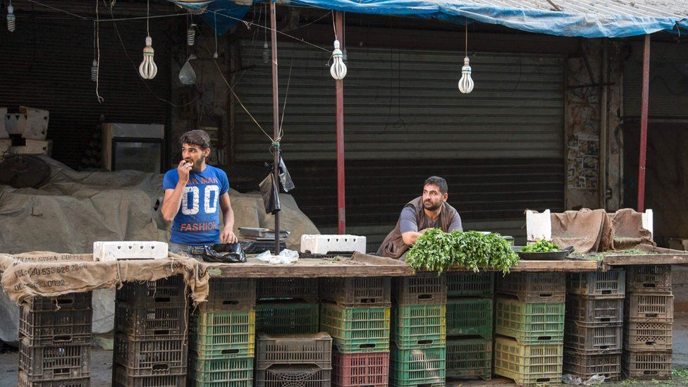 Syrians sell a few items at a market in the rebel-held area of the northern Syrian city of Aleppo on September 19, 2016, after humanitarian relief failed to enter the city under siege.