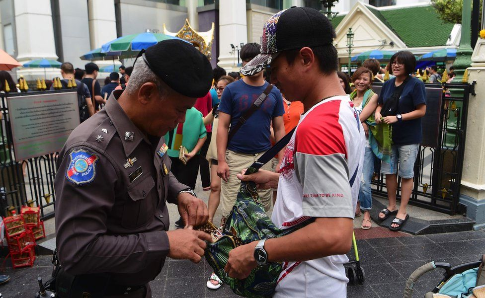 A Thai policeman searches a visitor's bag at the Erawan Shrine, Bangkok, on 13 August 2016.