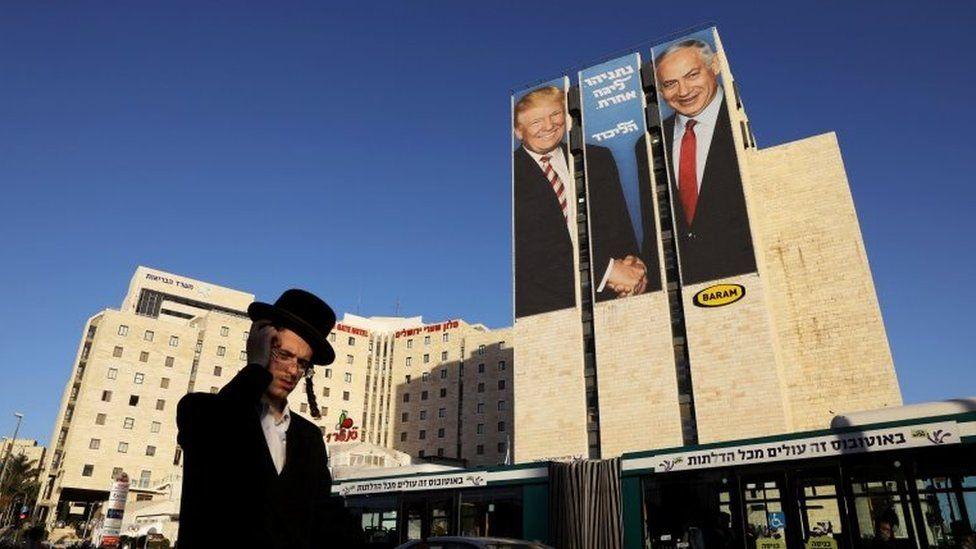 A man walks past a Likud election campaign billboard, depicting U.S. President Donald Trump shaking hands with Israeli Prime Minister Benjamin Netanyahu, in Jerusalem on 4 February 2019.