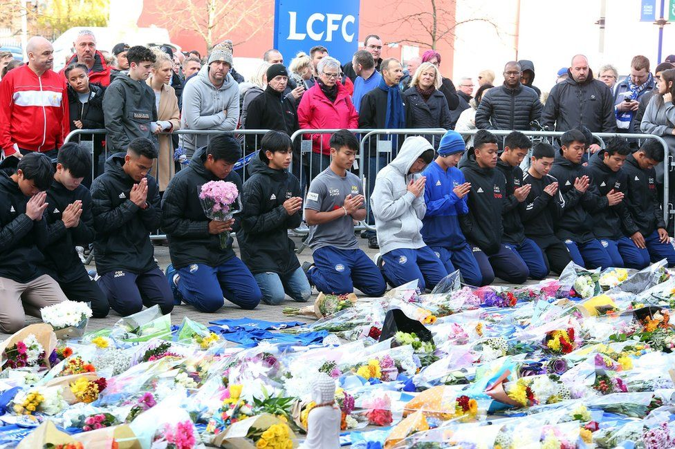 Players of the Fox Hunt Football Academy from Chaiyaphum in Thailand arrive to pay their respects outside the King Power stadium in Leicester, Britain, 28 October 2018